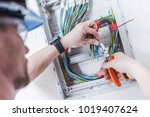 Electrical System Installation by Professional Caucasian Electrician. Construction and Power Industry Theme. - stock photo