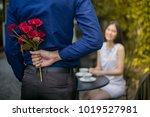 man is hiding flowers behind... | Shutterstock . vector #1019527981