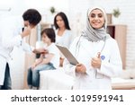 an arab doctor in hijab poses... | Shutterstock . vector #1019591941