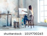 young woman artist painting at... | Shutterstock . vector #1019700265
