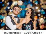 Stock photo celebration fun and holidays concept happy couple posing with party props over festive lights 1019725957