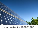 Solar Panel Against Blue Sky With Green Tree - stock photo