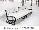 bench in the park after snowfall | Shutterstock . vector #1020058321