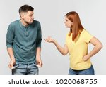 Small photo of Woman demanding money from her husband who is showing empty pockets on light background