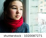 sad teen girl looks out the... | Shutterstock . vector #1020087271