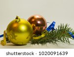 Small photo of New Year's gold-plated and pink glass Christmas balls and blue ribbon with a sycophant spruce on a white background