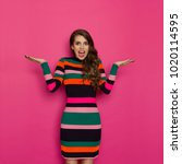 Stock photo beautiful young woman in colorful vibrant striped dress is holding hands raised looking at camera 1020114595
