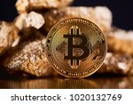 Small photo of Encrypted golden bitcoin lying in front of blurred gold lumps being most important finance trends nowadays on black background. Virtual digital electronic money currency blockchain futuristic finance