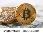 Small photo of Shiny golden bitcoin and gold lump put on dollar banknote and represent new financial trends. Blockchain digital virtual web electronic money mining exchange futuristic business innovation banking