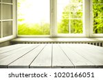 Small photo of Table background of free space and window with spring view. Empty place for your product or text.