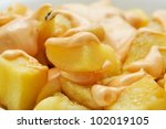 closeup of a plate with typical spanish patatas bravas, spicy potatoes - stock photo
