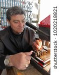 Small photo of Locksmith in workshop makes new key in Sofia, Bulgaria – sept 9, 2015. Professional making key in locksmith. Person who makes and repairs keys and locks. Key maker Machine and Accessary.