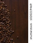 Small photo of Spilt coffee beans on wood surface table.