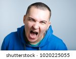 Small photo of portrait of an aggressive man screaming, wearing a blue hoodie, isolated on a gray background
