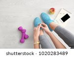 young woman tying shoelaces on... | Shutterstock . vector #1020283489