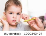mom feeds the child buckwheat... | Shutterstock . vector #1020343429