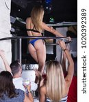 Small photo of Glad adult woman dancer gogo dancing in the night club on stage