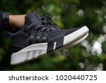 Small photo of Kuala Lumpur, Malaysia - February 6th, 2018 : A hand showing brand new sport shoes or sneaker produced by Adidas Originals EQT Bask ADV with blurred nature background. Selective focus.