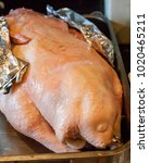 Small photo of uncooked goose with wings wrapped in aluminum foil
