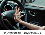 Small photo of Hand pushing the horn button of the steering wheel inside the car with an anger.