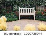 wood bench between flowerbed in ... | Shutterstock . vector #1020735049