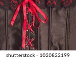 Small photo of The black silk corset is laced with a red ribbon.