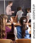 Male teacher in front of elementary age schoolchildren. - stock photo