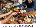 Small photo of Hands of cropped unrecognisable woman and man passing salad bowl at vegetarian restaurant.