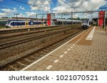 Small photo of Weesp, northern Netherlands - June 26, 2017. Locomotive stop on train station platform, railroad rails and blue cloudy sky at Weesp. Quiet and pleasant village full of canals and green near Amsterdam.