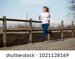 woman running in fall winter... | Shutterstock . vector #1021128169