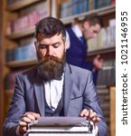 Small photo of Writers routine concept. Writer working on new book with bookshelves on background. Author types novel or poem. Man with beard and busy face sit in library and work with typewriter, close up.