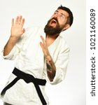 Small photo of Man with beard in white kimono on white background. Healthy lifestyle and sports concept. Karate man with scared face in uniform. Aikido master with black belt puts hands up in fear and yells