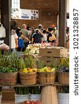 View of urban farmers market with baskets of vibrant vegetables in the foreground and people in the background.