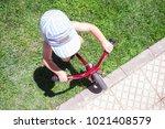 boy in blue cap riding a blue... | Shutterstock . vector #1021408579