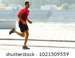 young sporty man jogging outdoor | Shutterstock . vector #1021509559
