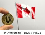 hand holding bitcoin on canada... | Shutterstock . vector #1021744621