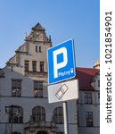Small photo of Blue paid parking sign with Adam Mickiewicz university building in the background on circa February 2018 in Poznan, Poland