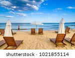 Small photo of Coastal landscape - man saunter along the sea against the background beach umbrellas and loungers, the Kavatsi bay near city of Sozopol in Bulgaria, September 15, 2017