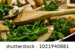 Small photo of Closeup view of wooden spoon stirring chicken and vegetables in cast iron skillet - Stir frying in the real world