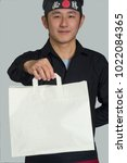 Small photo of Asian cook hold a take away white bag and wearing a black bandana with Chinese word ( victory )