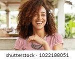 Small photo of Happy young pleasant looking African American female laughs at good joke, has fun together with best friend at cozy coffee shop, glad to meet and share positive news, have weekend or day off