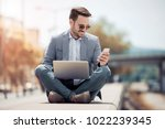 attractive man sitting outside  ... | Shutterstock . vector #1022239345