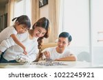 family saving money putting... | Shutterstock . vector #1022245921