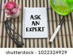 Small photo of glasses,marker pen,alarm clock,artificial bonsai and notebook written ask and expert over bamboo mat background