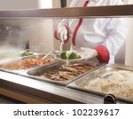 Stock photo chef standing behind full lunch service station 102239617