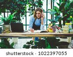 smiling saleswoman in floral... | Shutterstock . vector #1022397055