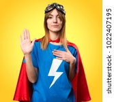 Small photo of Pretty superhero girl making an oath on colorful background