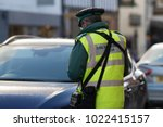 Small photo of traffic warden civil enforcement officer wearing reflective yellow vest issuing fixed penalty parking ticket fine