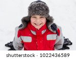 adorable smiling boy in winter... | Shutterstock . vector #1022436589