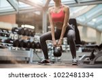 fit young woman squatting while ... | Shutterstock . vector #1022481334